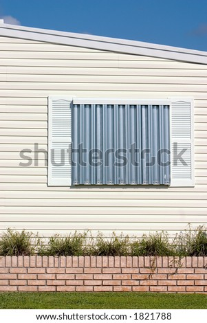 Hurricane protection corrugated metal panels installed on tropical home - stock photo
