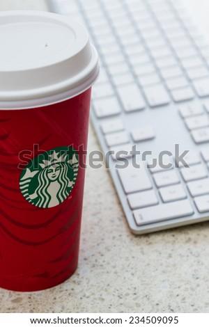 Hurricane Utah - November 29 : photo of a holiday Starbucks cup next to a computer keyboard, November 29 2014 in Hurricane, Utah - stock photo