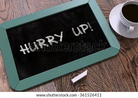 Hurry Up - Blue Chalkboard with Hand Drawn Motivation Quote and White Cup of Coffee on Wooden Table. Top View. - stock photo