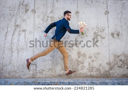 Hurrying to be in time. Side view of happy young man holding bouquet of flowers while running in front of the concrete wall - stock photo