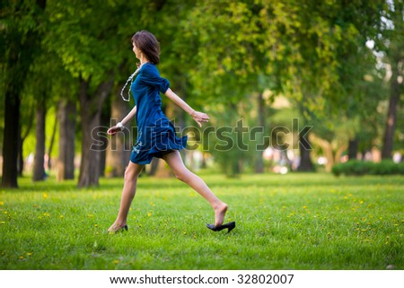 Hurrying woman walking fast throung park on a date - stock photo
