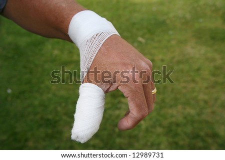 Hurt thumb with surgical dressing on the hand of an older man wearing a wedding ring - stock photo