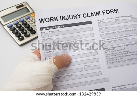 hurted hand holding a work injury claim form, medical and insurance concept - stock photo