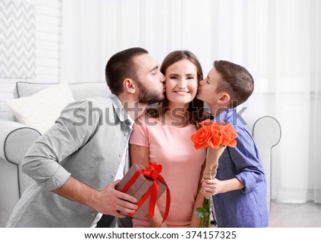 Husband and son giving gift box and roses to wife - stock photo