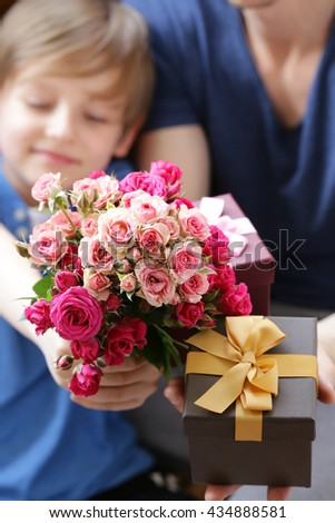 husband and son presented to  mom flowers and gifts - stock photo