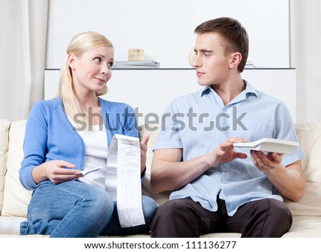 Husband and wife calculate the expenses sitting on the sofa