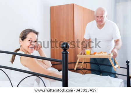 Husband and wife eating breakfast in bed.