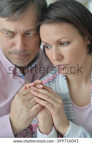 husband and wife holding hands sad - stock photo