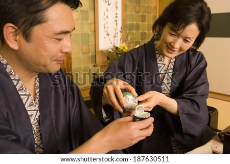 husband and wife in yukata pouring out alcohol drink - stock photo