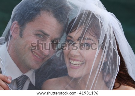 Husband and wife on wedding day under the veil
