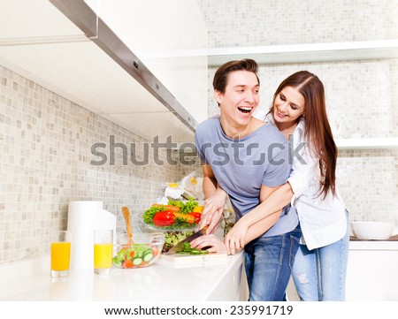 Husband and wife preparing food in the kitchen. - stock photo