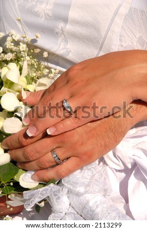 Husband and wife showing their wedding rings surrounded by the bride's bouquet. - stock photo