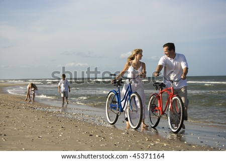 Husband and wife walk their bikes down the beach with children in the background. Horizontal shot. - stock photo