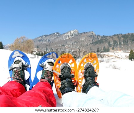 husband and wife with blue and orange snowshoes in the mountains - stock photo
