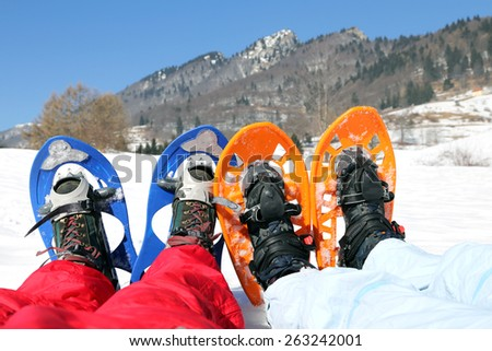 husband and wife with snowshoes in winter - stock photo