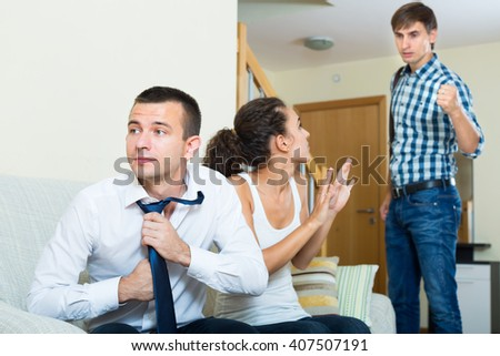 husband catching wife with lover on couch - stock photo