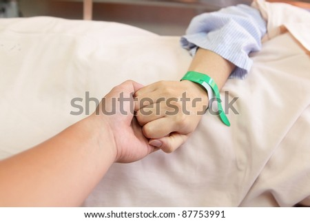 husband grip his wife's hand before surgery in an operation room - stock photo