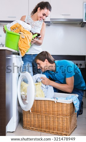 Husband helping happy russian housewife to use washing machine indoors - stock photo