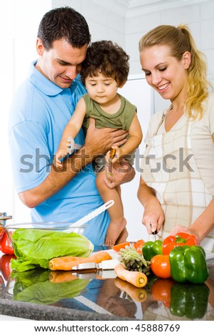husband holding baby boy in kitchen watching wife cooking food - stock photo