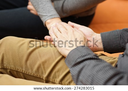 husband holding hands of his wife - stock photo