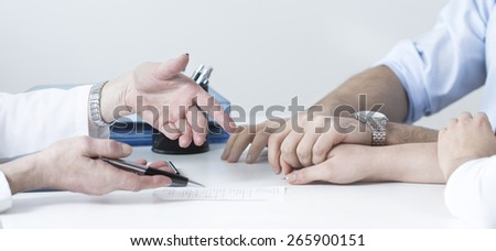 Husband holding wife's hand at doctor's office - stock photo