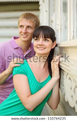 Husband hug wife near wooden village house, focus on wife - stock photo