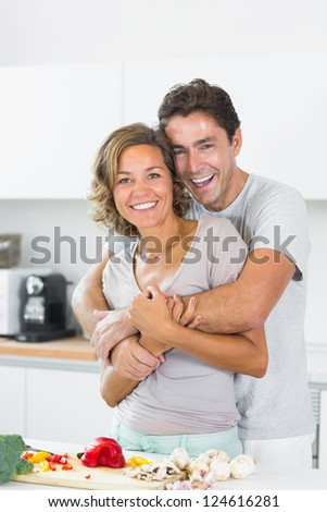 Husband hugging wife at the chopping board in the kitchen - stock photo