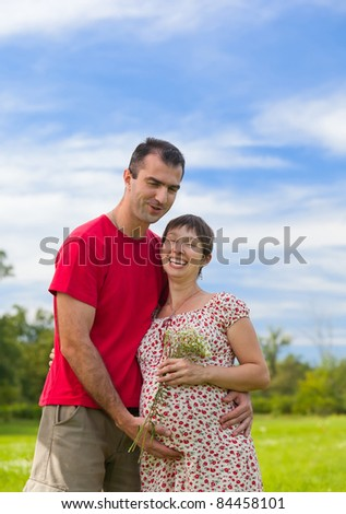 Husband hugs his pregnant wife outdoor - stock photo