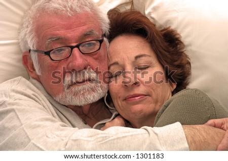 Husband hugs wife as she sleeps - stock photo