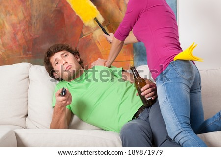 Husband ignoring his wife and watching tv on the couch - stock photo