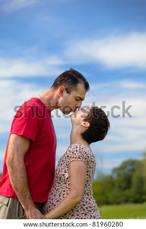Husband kiss his pregnant wife outdoor - stock photo