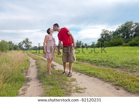 Husband kiss his pregnant wife, summer outdoor - stock photo