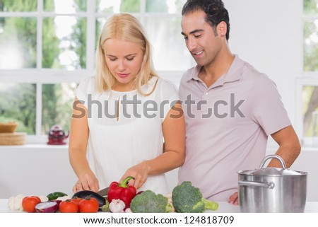 Husband looking at his wife cooking in the kitchen - stock photo
