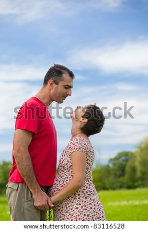 Husband looks at his pregnant wife oudoor - stock photo