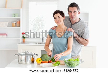 Husband massaging his wife while she is cutting vegetables in a kitchen