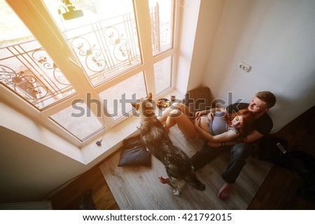 husband, pregnant wife and dog resting near a large window - stock photo