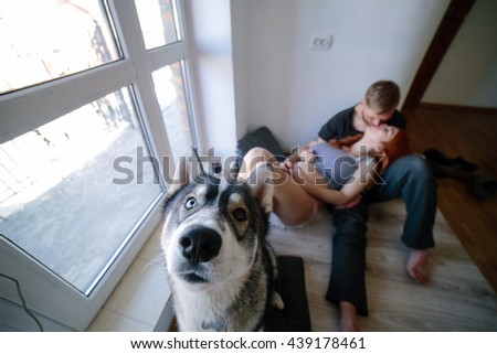 husband, pregnant wife and dog resting near a large window