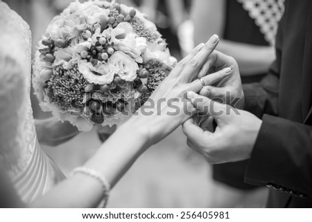 Husband puts a wedding ring on brides finger. Bride with wedding bouquet. Photo in black&white colors. - stock photo