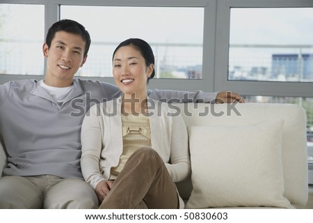 Husband Relaxing, arm behind wife on Sofa - stock photo
