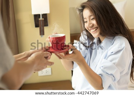 Husband serves coffee in bed to his wife and awaking her. focus a woman