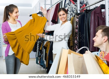 husband sitting with purchases, wife buying more clothes