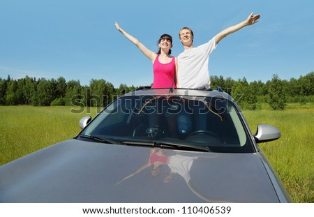 Husband, wife pose in hatch of car before hood in field - stock photo