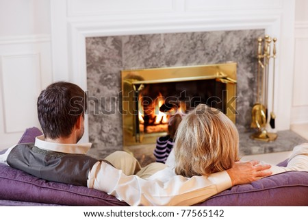 Husband & wife sit together on the sofa while their daughter reads by the fire - stock photo