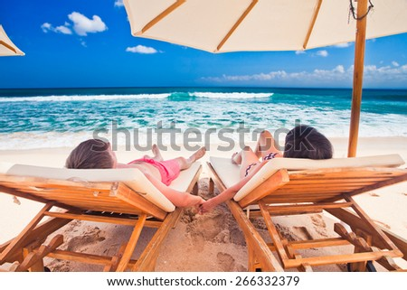 husband with his wife near blue ocean, couple just married on the beach - stock photo