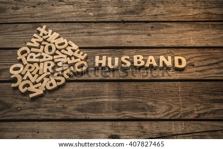 Husband word made of wooden brown letters on vintage wood table background. Empty space for inscription.
