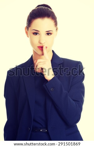 Hush. Businesswoman with finger on her lips gesturing for quiet - stock photo