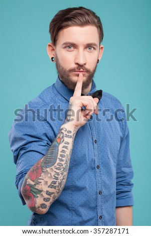 Hush-hush. Handsome young hipster is raising his index finger to her lips. He is standing and looking at camera seriously. Isolated on blue background - stock photo