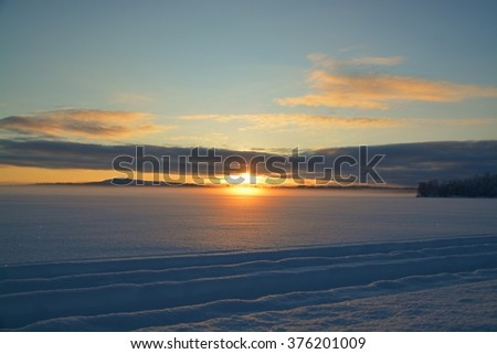 Husky sledge ride at sunset in winter wonderland (Lapland), motion blur - stock photo