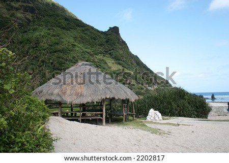 hut at a tropical beach with hills at the back