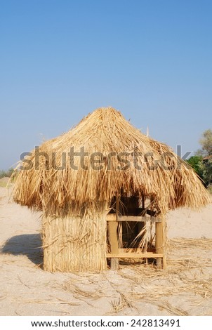 Hut from a dry grass ashore under blue sky - stock photo
